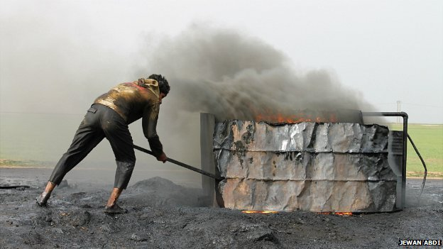 A young man works on a small oil refinery by the side of a road near the village of Gerhok