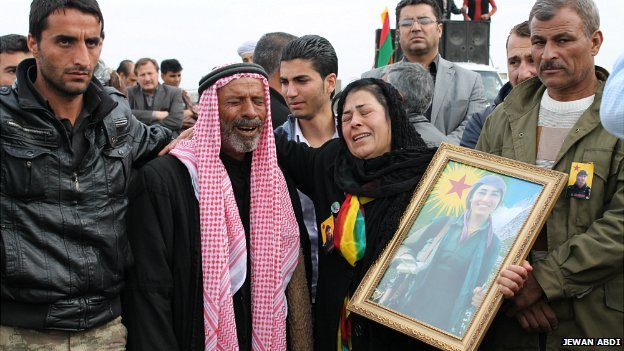 A grieving family attend the funeral of their daughter, who was killed by ISIS fighters