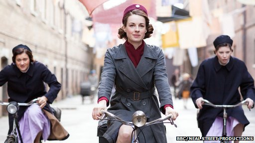 Jessica Raine riding bike with two students nurses puffing behind