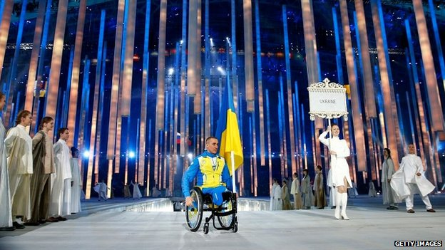 Mykhaylo Tkachenko carries the Ukraine flag at the opening ceremony of the Paralympics in Sochi