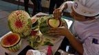 An Indian chef carves a watermelon