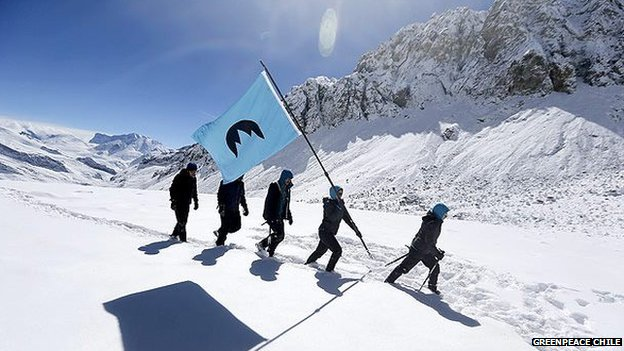 Activists hike through snow with Republica Glaciar flag