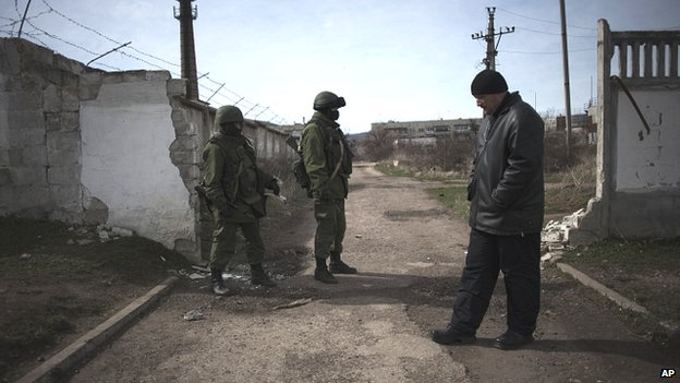A member of a pro Russian self-defence unit (right) stands close to Russian Army soldiers outside the Ukrainian army base in Perevalnoe, Crimea