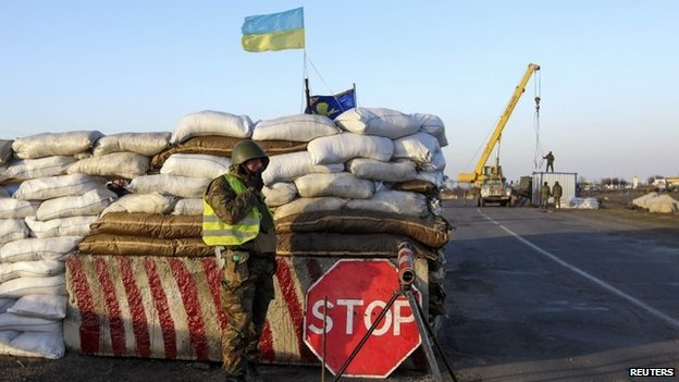 A Ukrainian soldier mans a checkpoint near the village of Salkovo, near the Ukrainian border with the Crimean region