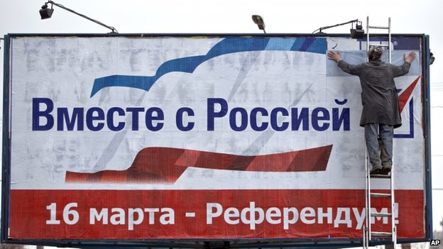 "A man pastes a poster advertising the referendum in Crimea that reads ""Together with Russia! March 16 - Referendum!"" in Simferopol, Ukraine"