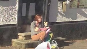 Woman breast feeding her daughter in public