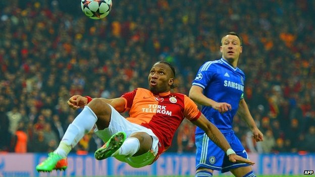 John Terry of Chelsea looks on as Didier Drogba of Galatasaray clears the ball during a match in Istanbul, Turkey on 26 February 2014