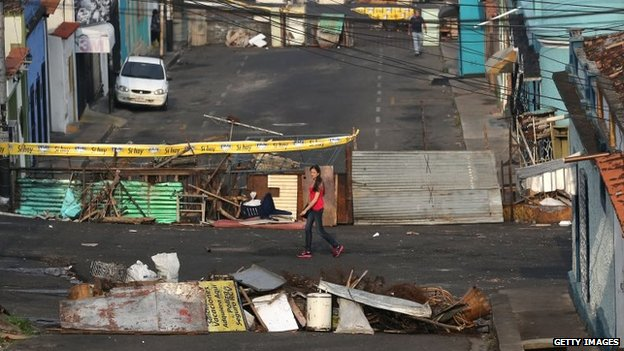 A woman walks past barricades in San Cristobal on 8 March, 2014