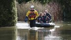 Couple leaving their flooded house in Chertsey by boat
