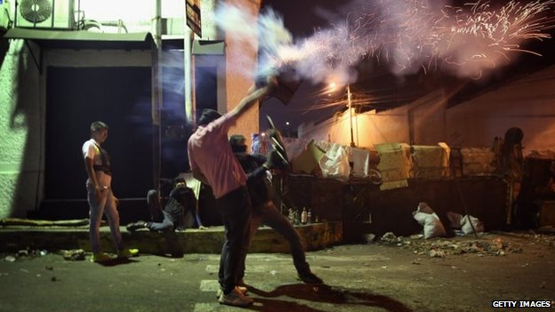 Students fire a homemade mortar tube towards security forces in San Cristobal before dawn on 9 March, 2014