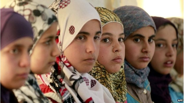 """Syrian refugee girls sit at the UNICEF """"Child Friendly Spaces"""" in the Zaatari refugee camp, near the Jordanian border with Syria"""