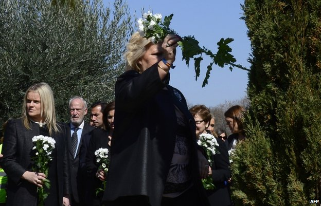 Angeles Pedraza places a flower into a tree during a Madrid commemoration ceremony