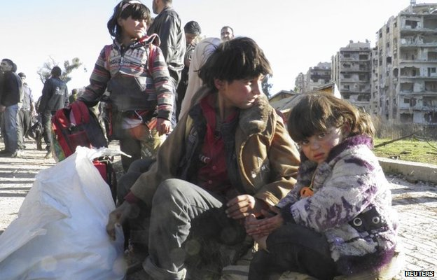 Children sit with their belongings as they wait to be evacuated from the Old City of Homs (12 February 2014)