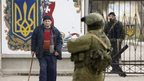 A man walks past an armed man (centre) guarding a Ukrainian base near Simferopol, Crimea