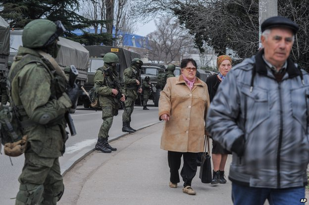 Troops in unmarked uniforms stand guard in Balaklava as people walk in a street, on the outskirts of Sevastopol, Ukraine, Saturday, March 1, 2014.