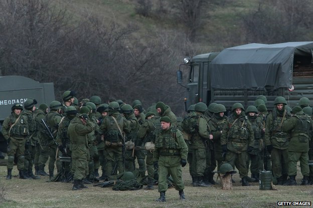Troops under Russian command assemble before getting into trucks near the Ukrainian military base they are blockading on March 5, 2014 in Perevalne, Ukraine.