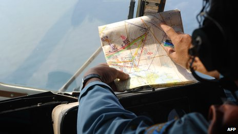 A crew member aboard a Vietnamese air force MI-171 helicopter checks a map during a search flight over the southern Vietnamese waters off Vietnam's island Phu Quoc