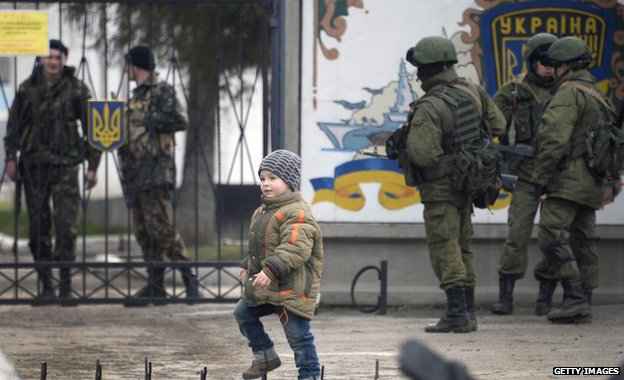 A boy passes by Russian forces blocking access to the base of the 36th detached brigade of the Ukrainian Navy's coastal guards, as Ukrainian soldiers stand guard behind the entrance gate, not far from the village of Perevalne, near Simferopol, on March 5, 2014.