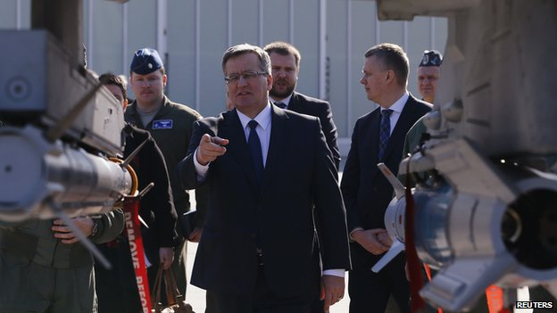 Polands President Bronislaw Komorowski points at missiles placed under a wing of a F-16 fighter jet as he visits the Lask airbase in central Poland March 11, 2014