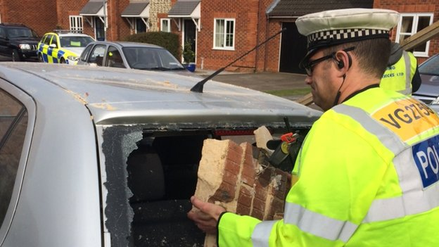 Police officer lifting bricks out of car