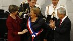 Chile's new President Michelle Bachelet (center) receives the presidential sash from Senate President Isabel Allende (left) after being sworn in during a ceremony before congress in Valparaiso on 11 March, 2014