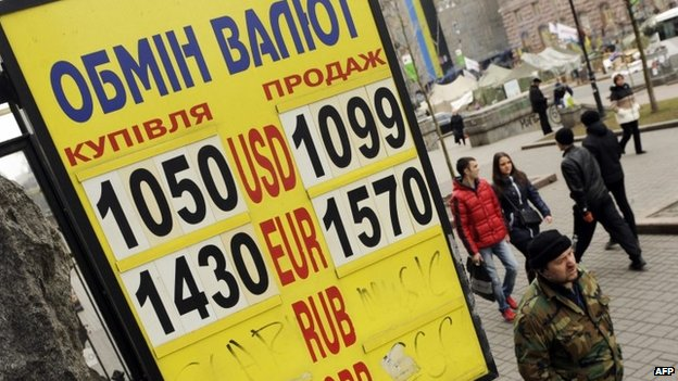 People in Kiev walk past a currency exchange board