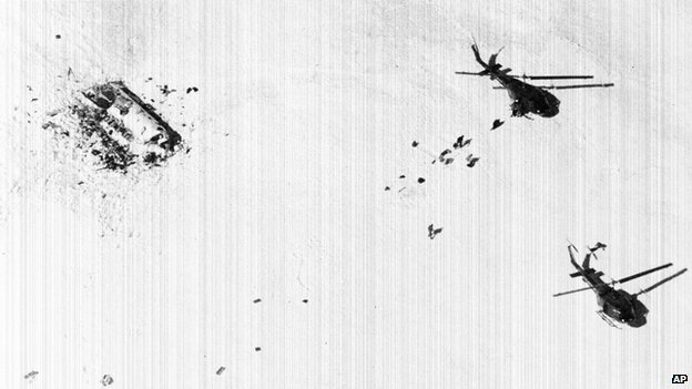 Survivors of the Uruguayan plane crash in the Andes walk across snow toward rescue helicopters in December 1972