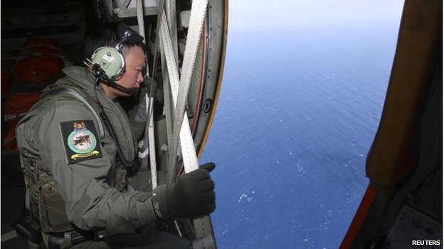 A member of military personnel looks out of a Republic of Singapore Air Force C130 transport plane during the search for the missing Malaysia Airlines plane