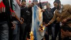 Jordanian demonstrators burn an Israeli flag during a protest in front of the parliament in Amman on 11 March 2014.