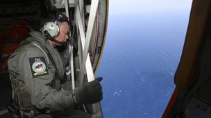 A member of military personnel looks out of a Republic of Singapore Air Force C130 transport plane during a search for the missing Malaysia Airlines MH370 plane over the South China Sea, 11 March 2014