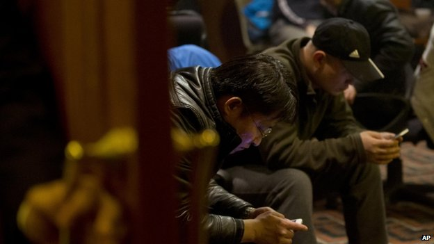 Chinese relatives of passengers aboard a missing Malaysia Airlines plane browse their smartphone for the latest news inside a hotel room set aside for relatives or friends of passengers aboard the missing airplane in Beijing, China Wednesday, 12 March 2014