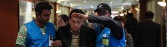 Malaysia Airline special assistance team members help a relative of a passenger onboard Malaysia Airlines flight MH370 at Lido Hotel on 11 March 2014 in Beijing, China