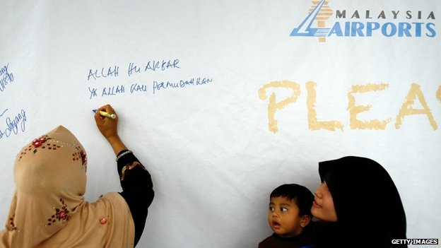 Malaysian woman writes message on a wall in Kuala Lumpur (12 March 2014)