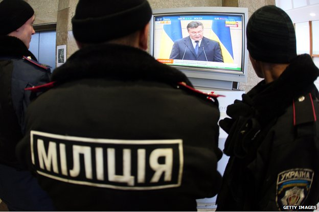 Police officers guarding the regional state administration building in Donetsk watch the televised speech of former Ukrainian President Viktor Yanukovych during his press conference in the Russian city of Rostov-on-Don on March 11, 2014.