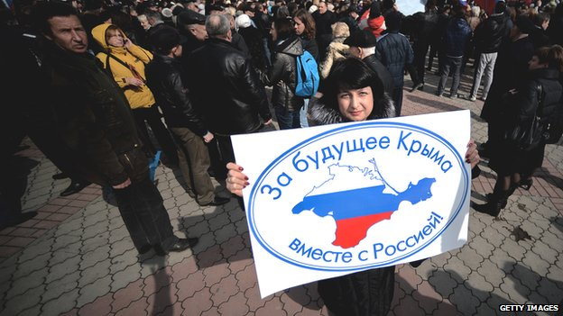 "Pro-Russian demonstrator in Crimea, with sign reading, ""For Crimea's future with Russia"""