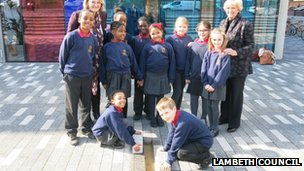 Lambeth Council leader Lib Peck and Diane Towler-Green MBE with children from Granton Primary School laying the final stones over the time capsule