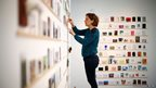 """Gloria Cevallos puts up postcards at the Royal College of Art's annual """"secret"""" art exhibition"""