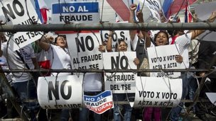 "Supporters of Norman Quijano, many holding posters that read in Spanish; ""No to electoral fraud,"" demand a vote recount of Sunday's runoff election in San Salvador on 11 March, 2014"