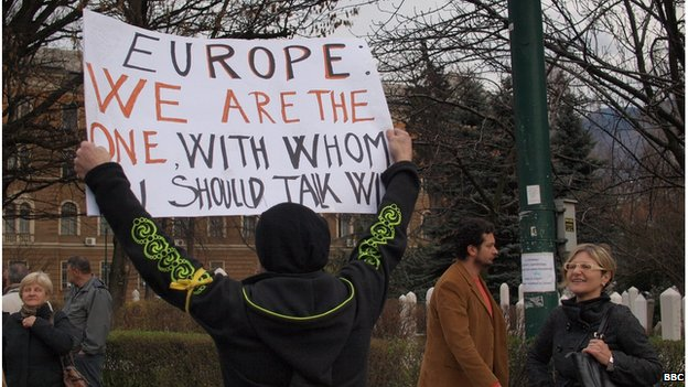 "A protester holding a sign reading ""Europe: We are the one with whom U should talk"""