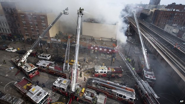Firefighters battle a fire after a building collapse in East Harlem, New York, on 12 March 2014