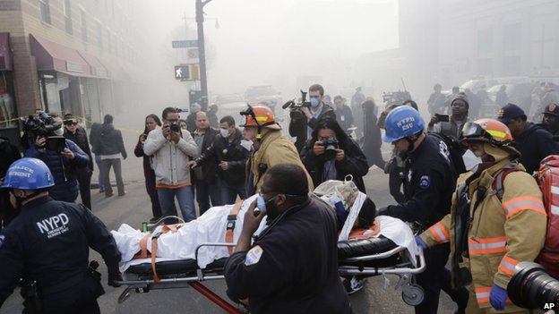 Rescue workers remove an injured person on a stretcher after an explosion and building collapse in the East Harlem, New York, on 12 March 2014