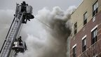 Firefighters try to extinguish a fire at the site of a building collapse in Harlem