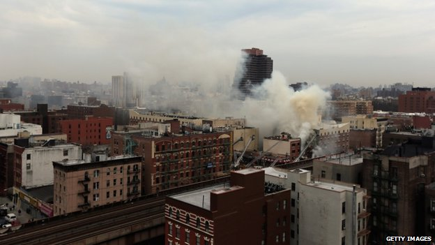 Smoke rises from a five-alarm fire and building collapse in New York City on 12 March 2014