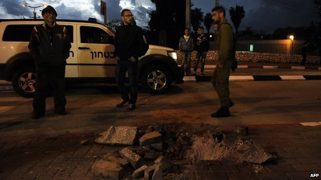 Israelis inspect the damage done by a rocket to a road in the town of Sderot (12 March 2014)