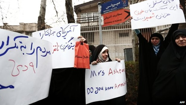 Members of the Basij militia hold banners criticising Catherine Ashton at a protest outside the Austrian embassy in Tehran on 12 March 2014