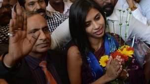 Indian diplomat Devyani Khobragade (R), accompanied by her father Uttam Khobragade, gives a traditional greeting on her arrival at the domestic airport in Mumbai 14 January 2014