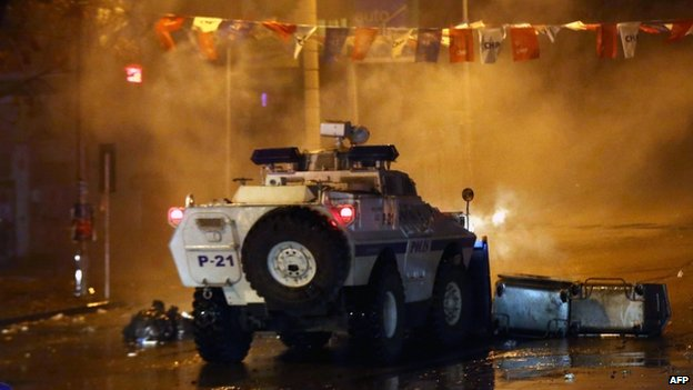 An armoured police vehicle drives through a barricade in Ankara (12 March 2014)