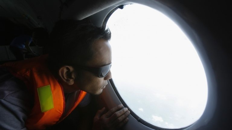 A Malaysian journalist looks for the missing Malaysia Airlines flight MH370, during a mission on a Vietnam Air Force aircraft AN-26, off Con Dao island, 13 March 2014