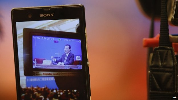 A reporter takes pictures of Chinese Premier Li Keqiang from a video camera screen during a press conference after the closing ceremony for the annual National People's Congress in Beijing's Great Hall of the People, China, Thursday, 13 March 2014
