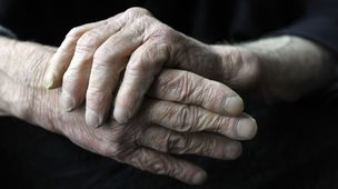Elderly male rubbing his hands together